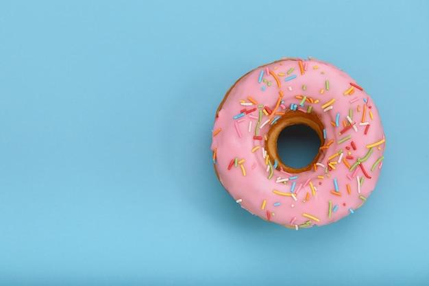 Roze donut op een blauw oppervlak, bovenaanzicht, concept van desserts, roze kleur op blauw