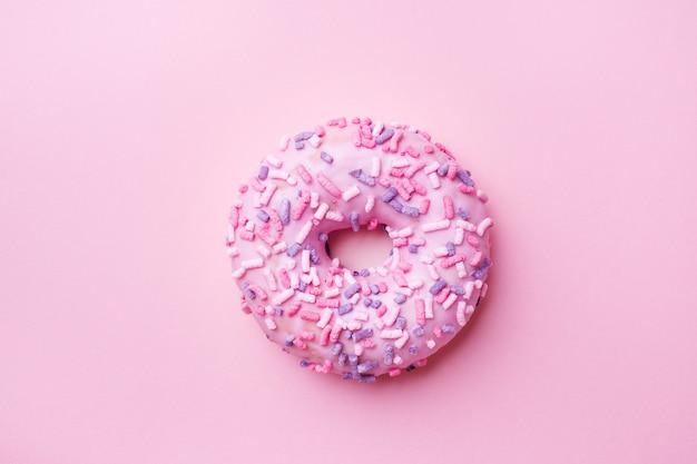 Roze donut op roze. bovenaanzicht plat leggen.
