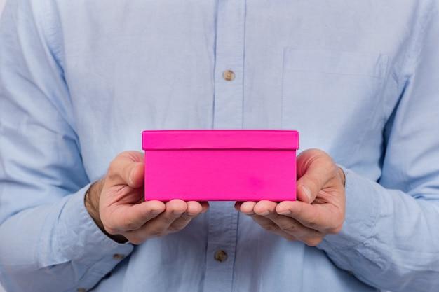 Roze doos in handen van de mens. man geeft cadeau. express levering van geschenken. vooraanzicht.
