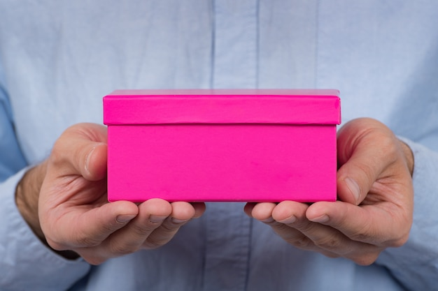 Roze doos in handen van de mens. man geeft cadeau