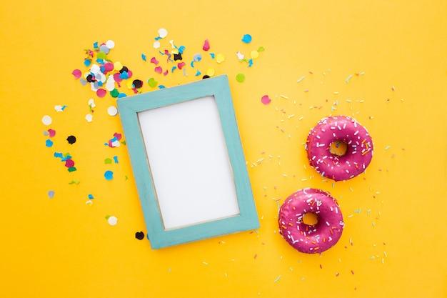 Roze doughnut en frame met copyspace op gele achtergrond