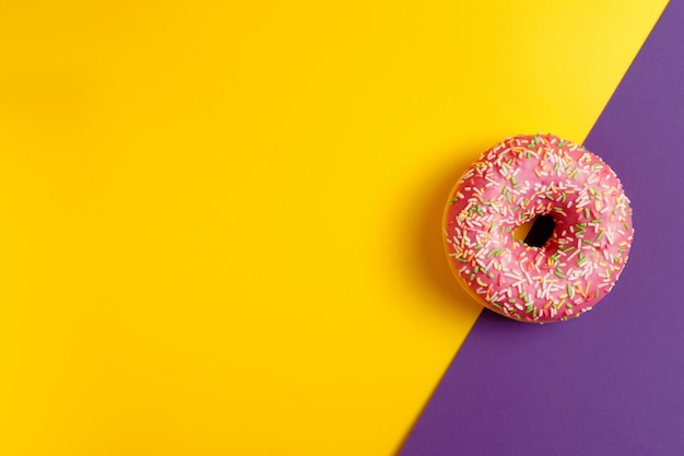 Roze doughnut op de gele en violette donkerpaarse ruimte van het achtergrond hoogste meningsexemplaar