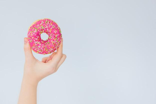 Roze doughnut ter beschikking op een grijze muurachtergrond