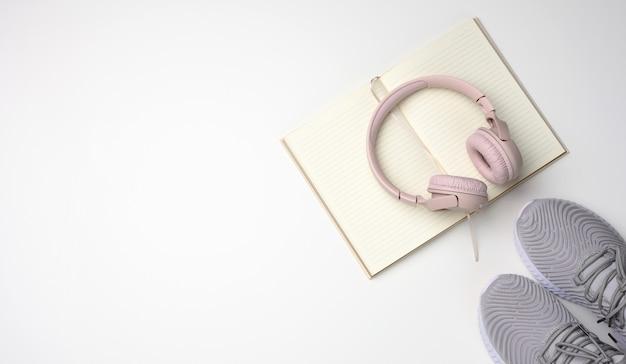Roze draadloze koptelefoon, een paar grijze sneakers en notitieblok op een witte achtergrond, bovenaanzicht. vrouwenkleding