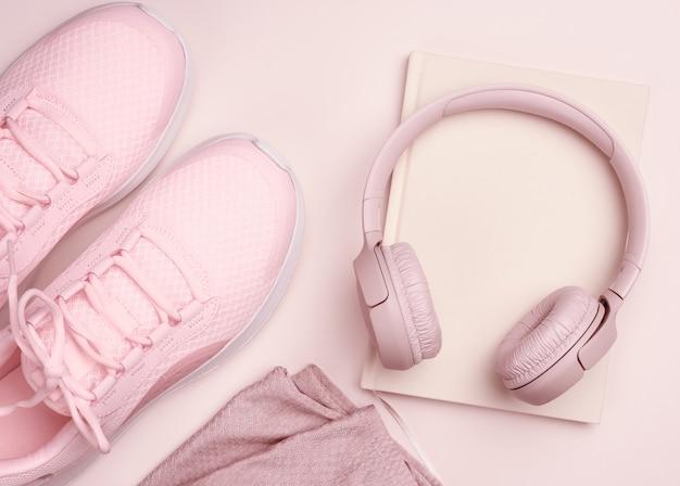 Roze draadloze koptelefoon, een paar sneakers en een notitieblok op een beige achtergrond, bovenaanzicht. vrouwenkleding