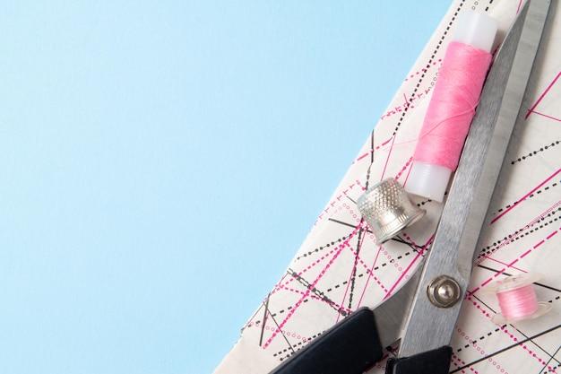 Roze draadrollen en schaarpatroon en accessoires voor handwerk op blauw