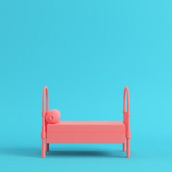 Roze eenpersoonsbed met kussen op helderblauwe achtergrond
