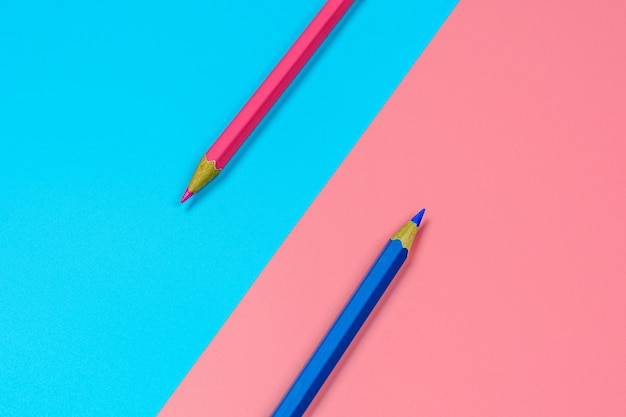 Roze en blauw kleurpotloodpotlood op blauwe en roze achtergrond.