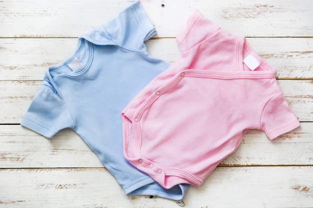 Roze en blauwe babypakje op witte houten achtergrond