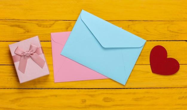 Roze en blauwe envelop, geschenkdozen, hart op gele houten