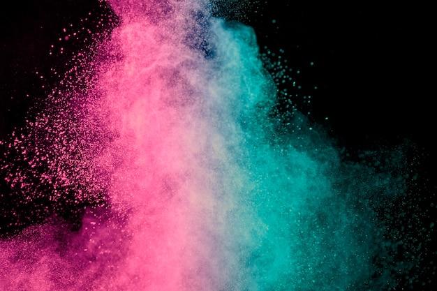 Roze en blauwe explosie van make-uppoeder op donkere achtergrond