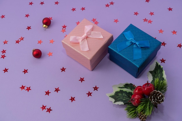 Roze en blauwe geschenkdozen met een strik op een lila achtergrond, confetti en kerstdecor