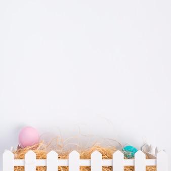 Roze en blauwe paaseieren tussen hooi in doos
