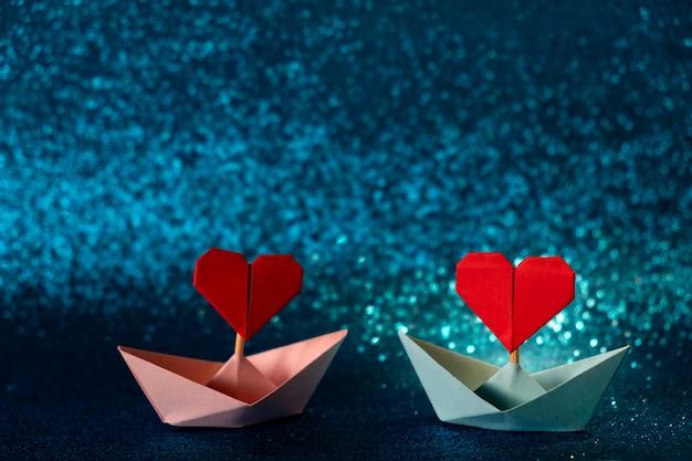 Roze en blauwe papieren boot op glitter blauwe achtergrond. romantisch, valentijnsdag concept met ruimte voor tekst.