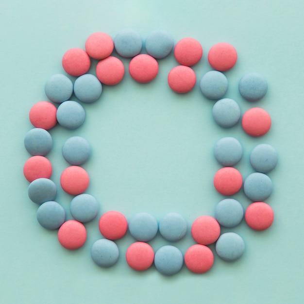 Roze en blauwe snoepjes gerangschikt in cirkelvorm over de gekleurde achtergrond