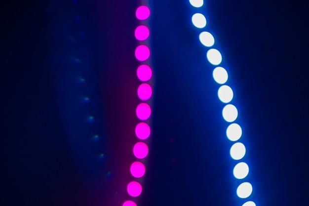 Roze en blauwe wazige neon bokeh lichten op zwart. abstracte achtergrond van jaren 80 kleuren.
