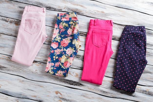 Roze en donkerblauwe broek. stijlvolle broek op houten ondergrond. koopwaar van de beste fabrikant. origineel ontwerp en heldere kleur.