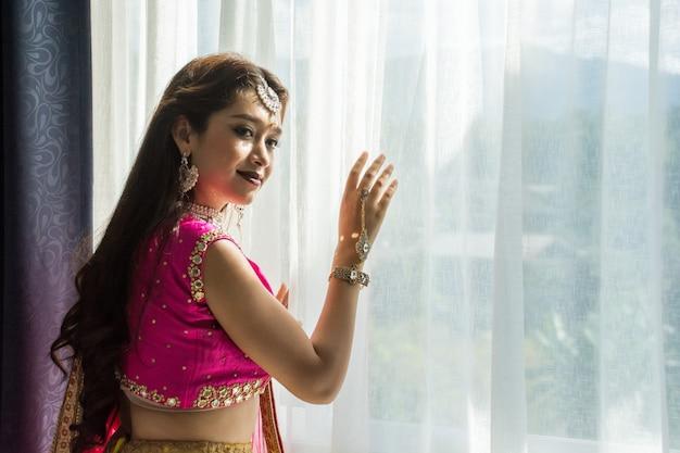 Roze en geel indisch kostuum mooi meisje, gezicht gedeeltelijk bedekt met saree.