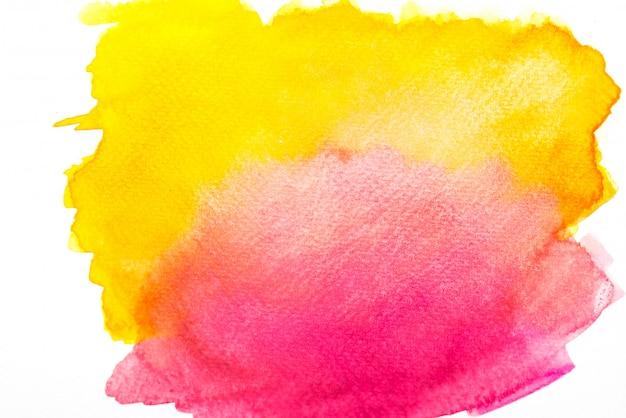 Roze en gele aquarel spatten op het papier.