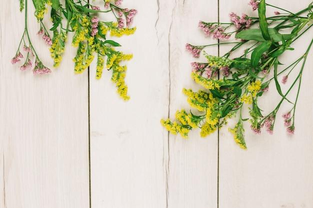 Roze en gele guldenroede of solidago gigantea bloeit over het houten bureau