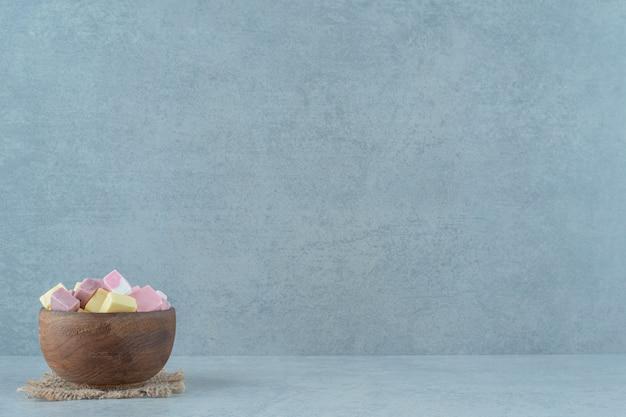 Roze en gele marshmallow-snoepjes in een houten kom op een witte ondergrond