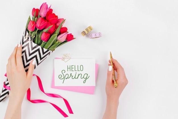 Roze en goud gestileerd bureau met bloemen. vrouwelijke handen houden bloemen vast