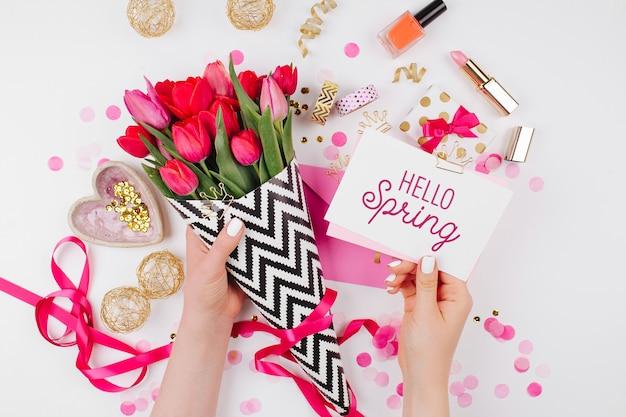 Roze en goud gestileerd bureau met bloemen. vrouwelijke handen houden kaart vast