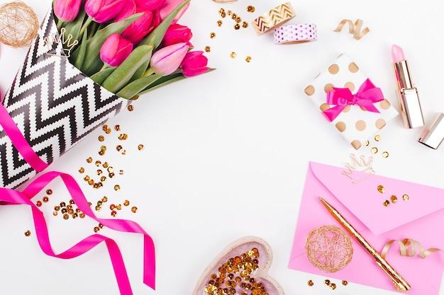 Roze en goud gestyled bureau met bloemen. roze tulpen in zwart-wit stijlvol inpakpapier, geschenken, cosmetica en vrouwelijke accessoires met confetti op witte achtergrond