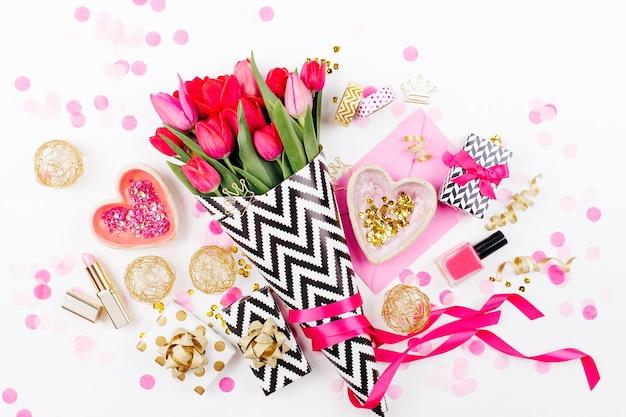 Roze en goud vormgegeven bureau met bloemen roze tulpen cosmetica en vrouwelijke accessoires
