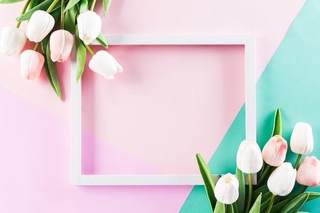 Roze en groene muur met fotolijst en tulp bloemen