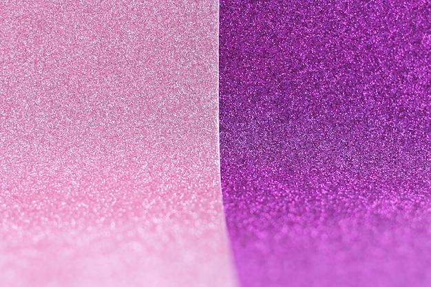 Roze en paars gebogen gliterpapier. ruimte voor tekst.