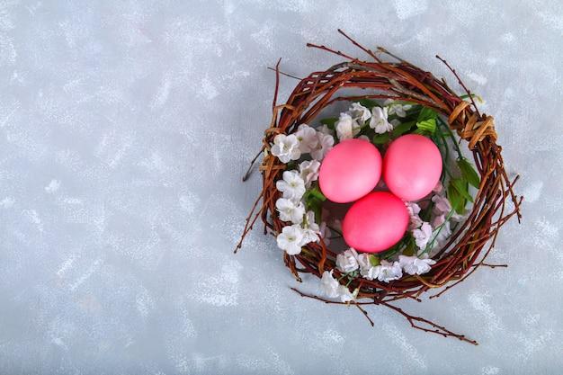 Roze en paarse paaseieren in een nest met witte bloemen op een grijze concrete achtergrond.
