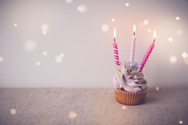 Roze en paarse verjaardag cupcake met drie kaarsen