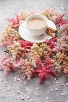 Roze en rode astilbe bloemen en een kopje koffie op een grijze concrete achtergrond