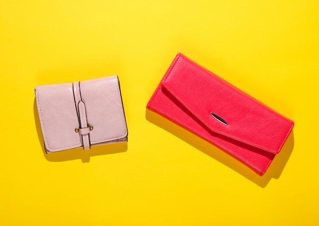 Roze en rode lederen portefeuilles op een gele tafel. bovenaanzicht