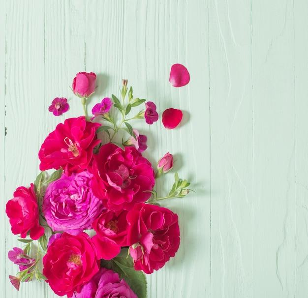 Roze en rode rozen op groene houten achtergrond