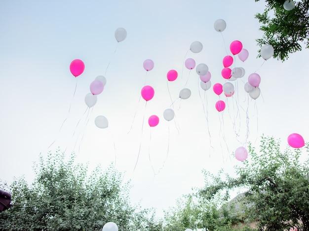 Roze en witte ballonnen vliegen weg in de lucht
