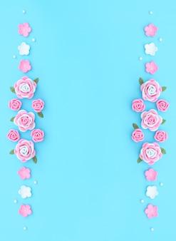Roze en witte bloemen gemaakt van foamiran met groene bladeren en witte kralen op blauwe achtergrond.