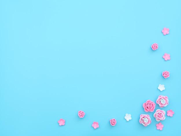 Roze en witte bloemen gemaakt van foamiran op blauwe achtergrond met kralen.