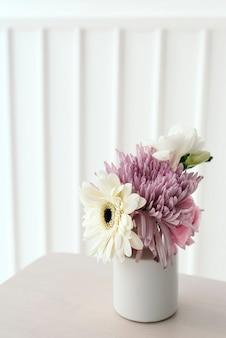 Roze en witte bloemen in een witte vaas