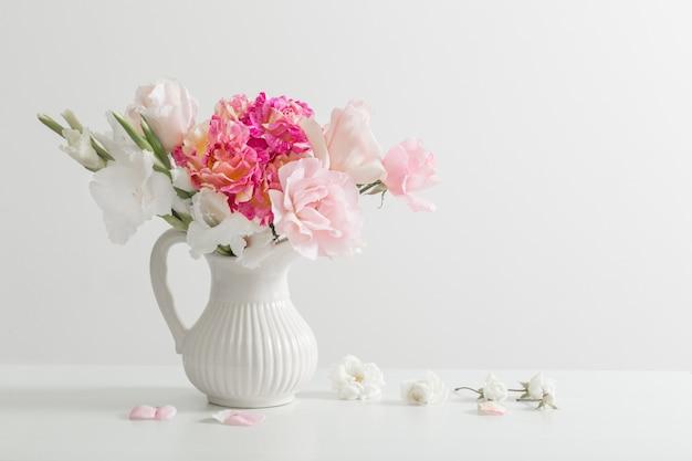 Roze en witte bloemen in vaas op witte tafel