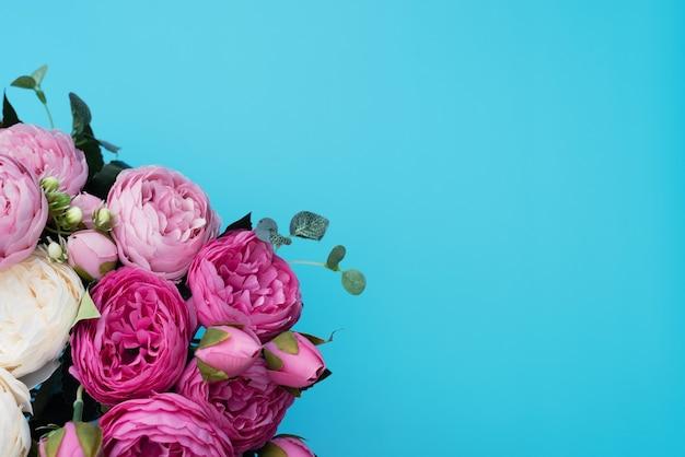Roze en witte bloemen op blauwe achtergrond.