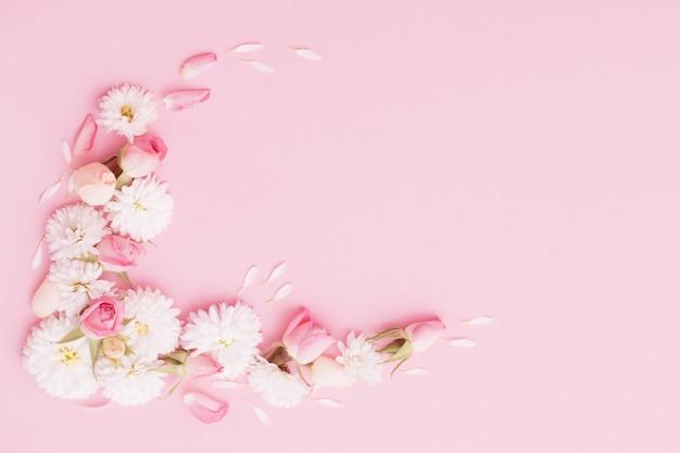 Roze en witte bloemen op roze papieren achtergrond Premium Foto