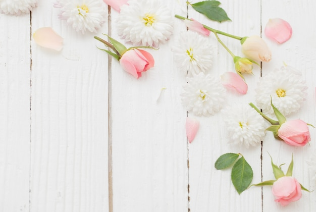 Roze en witte bloemen op witte houten achtergrond