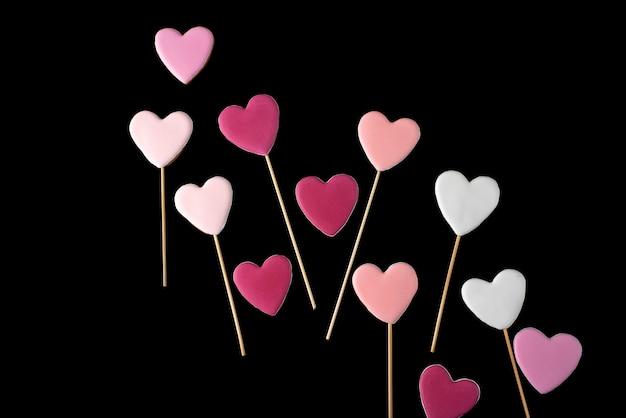 Roze en witte cookies op een stok in de vorm van harten op een zwarte geïsoleerd. valentijnsdag.