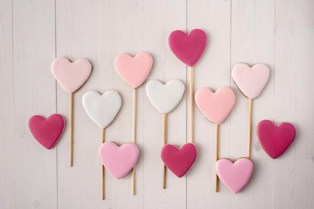 Roze en witte koekjes op een stok in de vorm van harten. valentijnsdag.