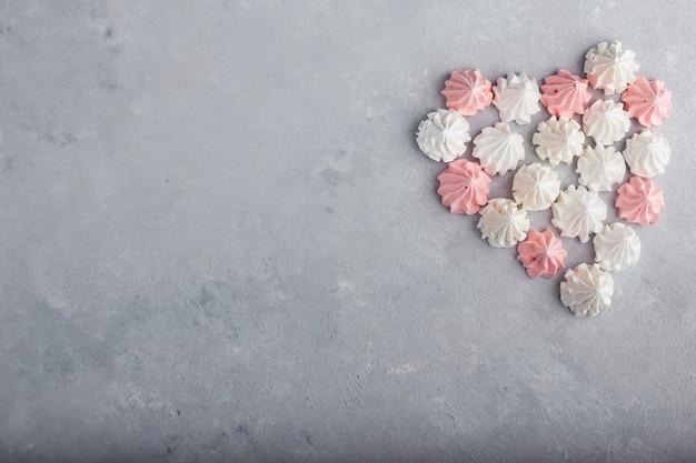 Roze en witte marshmallows in een hartvorm.