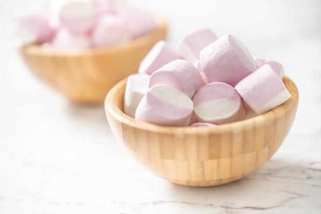 Roze en witte marshmallows in een volledig houten kom geplaatst op een marmeren oppervlak met een focus op de kom aan de voorkant.