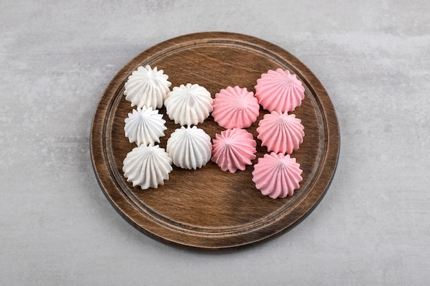Roze en witte meringue op een bord, op de marmeren tafel.