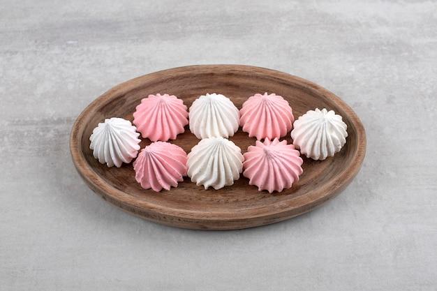 Roze en witte meringue op een bord, op het marmer.